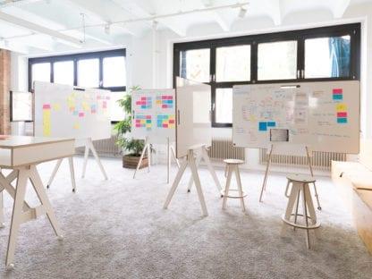 kreativer Workshopraum mit Whiteboards und Stehtischen