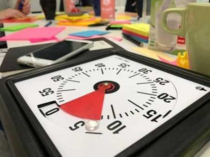 TimeTimer auf Tisch mit Post-its, Handy und anderen Dingen.