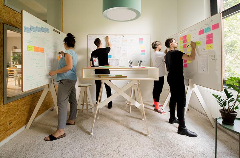 Vier Menschen arbeiten an Whiteboards